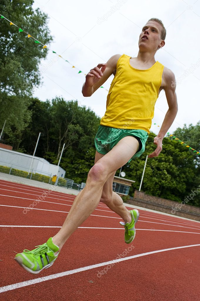Running athlete on a middle distance race on an oval track in mid-air — Lizenzfreies Foto #2136842