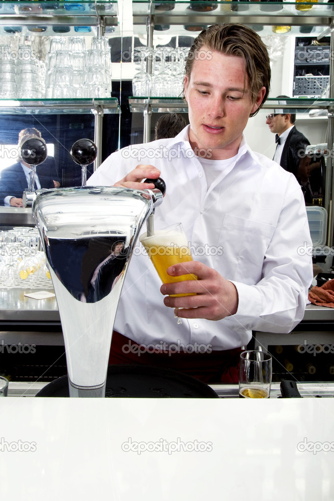 A bartender tapping a beer from his beer pump with customers in the reflection of the mirror — Stock Photo #2137993