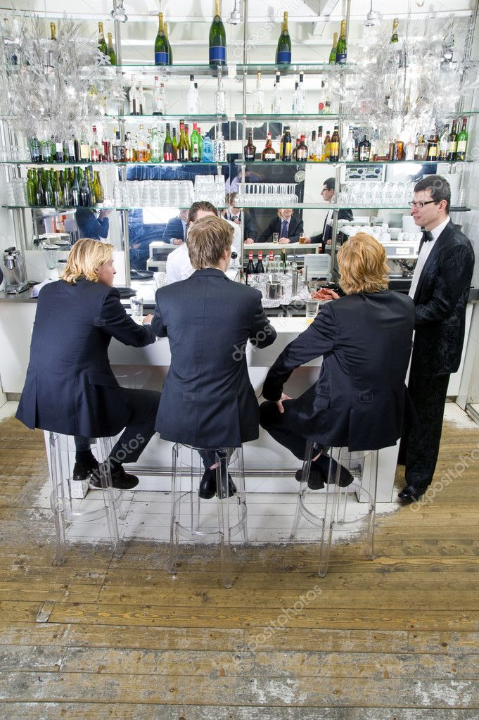 Four customers and a barkeeper sitting, standing, talking and drinking at a bar  Stock Photo #2141496