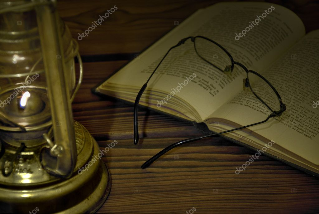 Old style lamp lighting on a book — Stock Photo #2087786