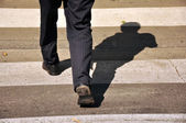 Shadow of a mail pedestrian croosing the road — Stock Photo