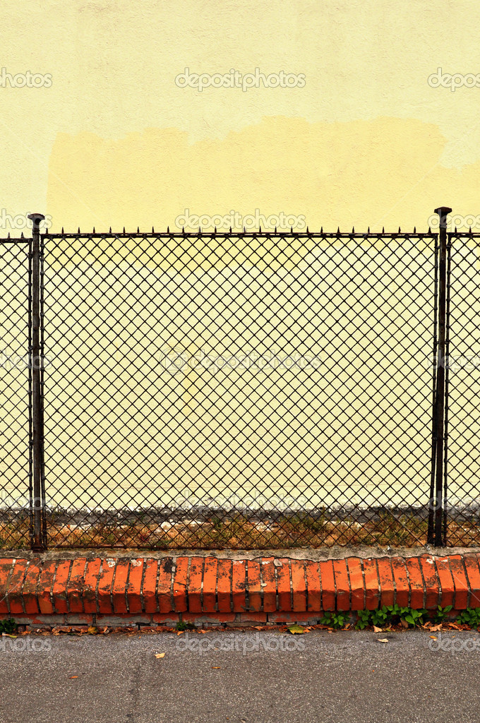 Detail of a steel fence against a yellow concrete wall. — Stock Photo #2095305