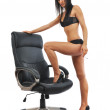 Sexy young woman posing in leather chair — Stockfoto