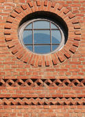Brick wall with a round window — Stock Photo