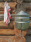 Towels and wash basin on wooden wall — Stock Photo