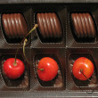 Cherries and chocolate candies in a box — Stock Photo