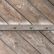 Stock Photo: Old wooden door with an iron strip