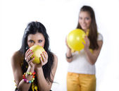 Girl with fruit and girl with balloon — Stock Photo