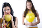Girls with yellow balloon and fruit — Stock Photo