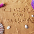 Closed for holidays written on sand — Stok fotoğraf