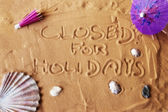 Closed for holidays written on sand — Stock Photo