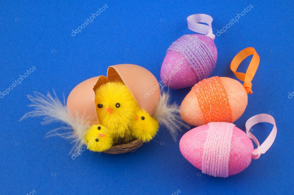 Close-up shot of a broken egg with hatching chicks. Three colorful easter eggs on the left. Blue background. — Stock Photo #2199542