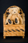 Teddy on African ethnic chair — Stock Photo