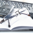 Notebook,glasses, keyboard — Stock Photo