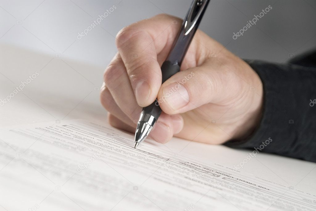 Man holding a pen writing his signature — Stock Photo #2240307