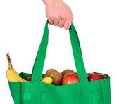 Transportant des produits d'épicerie dans un sac vert réutilisable — Photo
