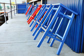 Red and Blue Stools Leaning Against Bar — Stock Photo