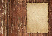Old wrinkled paper on wood — Stock Photo