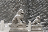 Lion statue and old wall after snow — Stock Photo