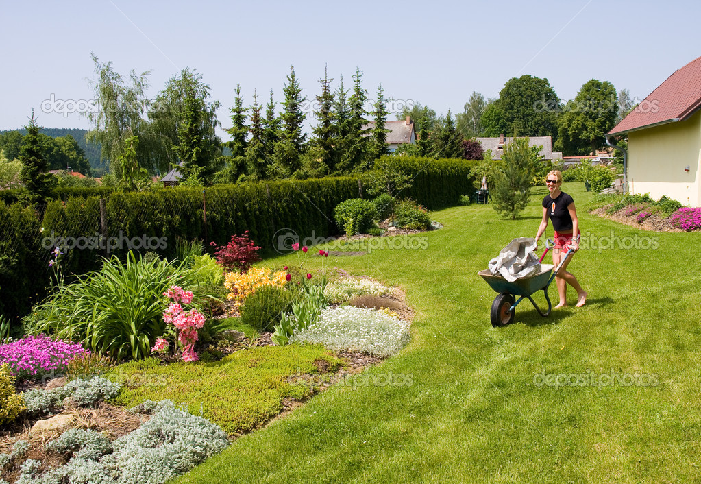 Young female gardening with a wheelbarrow — Stock Photo #2183068