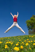 Young woman in red outfit having fun on meadow — Stock Photo