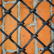 Stock Photo: Pattern of iron grid and red brickwall