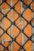 Pattern of iron grid and red brickwall — Stock Photo