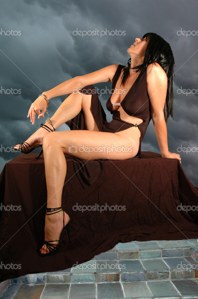 Brunette woman handcuffed to alter in storm.  Stock Photo #2325606