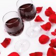 Stock Photo: Wine glasses and rose petals