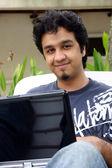 Genç adam bir dizüstü bilgisayar kullanarak — Stok fotoğraf