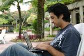 νεαρός άνδρας, χρησιμοποιώντας ένα φορητό υπολογιστή — Φωτογραφία Αρχείου