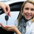 Happy woman receiving car key - Zdjęcie stockowe