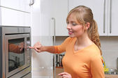 Blond woman cooking with microwave — Stock Photo