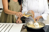 Cookery course: pouring wine into a pan — Stock Photo