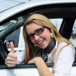feliz mujer conduciendo un coche nuevo — Foto de Stock