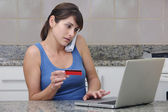 Woman with creditcard on phone — Stock Photo