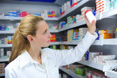 Pharmacist searching the right medicine — Stock Photo