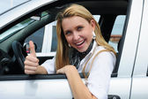 Happy woman driving a new car — Stock Photo