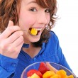 Young woman eating fruit salad — Stock fotografie