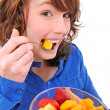 Foto Stock: Young woman eating fruit salad