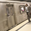 Royalty-Free Stock Photo: Black Businessman Watching the Metro Train Pass