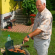Old man outside cooking/ barbecuing — Stock Photo