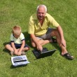 Grandfather and grandson working on lapt - Stock Photo