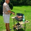 Old man outside cooking/ barbecuing - Stock Photo
