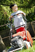 Young boy mowing grass in summer day — Stock Photo