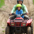 Dad with son riding a quad bike — Stock Photo
