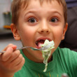 Young boy indoors eating — Stock Photo