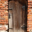 An old, rotten door in a brick wall - Stock Photo