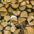 Stacked winter logs for heating on yello — Stock Photo