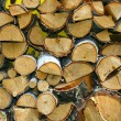 Stacked winter logs for heating on yello - Stock Photo